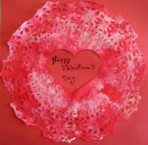 A sponge-painted doily with a heart-shape cut out of it (allowed to dry, then pasted on construction paper)