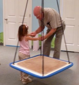 Virgil invites an elementary student to do Iso-Doodles (photo was taken in the therapy room, thus the swing).
