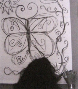 A student completes a Double Doodle butterfly design based on the Nines game.