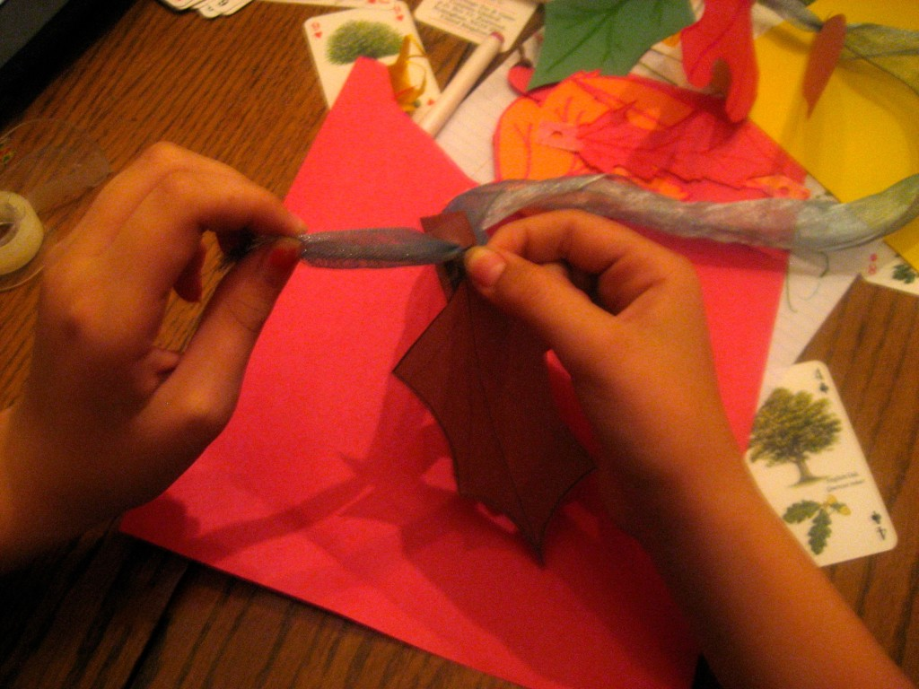 My granddaughter threads the leaves onto a silver ribbon she found in the gift recycle.