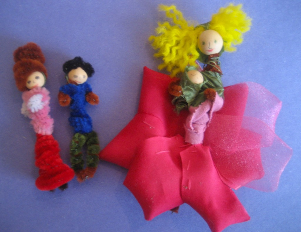 At right: A mother flower fairy cradles her infant (wrapped in a leaf) while a girl and boy fairy look on. The mother's sash, made of fabric scrap tied in the back, helps to hold the petals in place. For this photo, they are not wearing their wings.