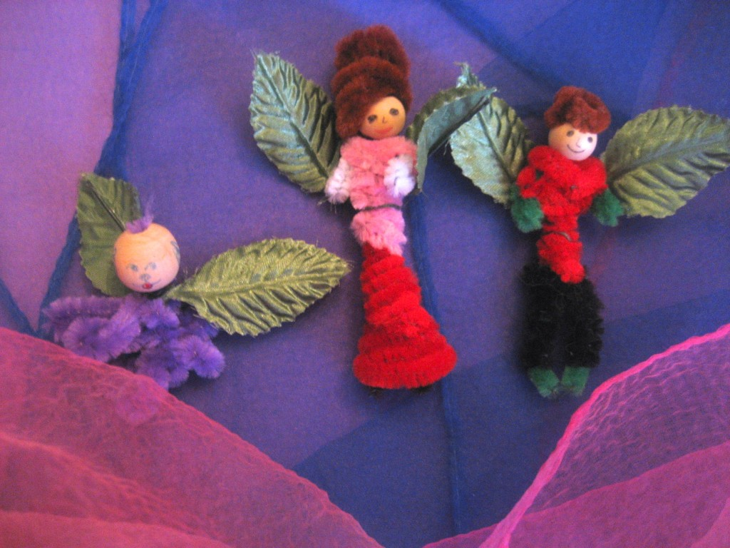 Two flower fairies frolic among the play scarves with their fairy dog.
